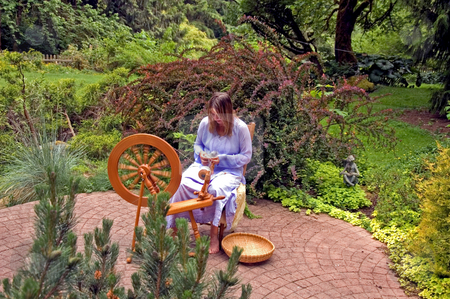 Woman Spinning stock photo, This Caucasian woman is an artisan hand spinning wool into yarn on her spinning wheel in her beautiful lush garden. by Valerie Garner