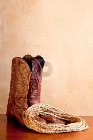 A vertical image of a pair of brown cowboy boots and a coil of r stock photo, A vertical image of a pair of brown cowboy boots and a coil of rope on a wooded surface with an old textured background by Vince Clements