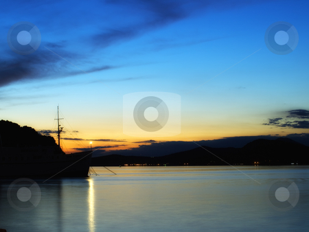 Tranquil harbor stock photo, Silhouette of the ship's bow that emerges from the surrounding relief in one of Adriatic ports. by Sinisa Botas