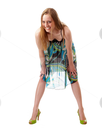 Smiling caucasian woman bending forward in dress stock photo, Woman in dress and heels with hands on knees by Jeff Cleveland