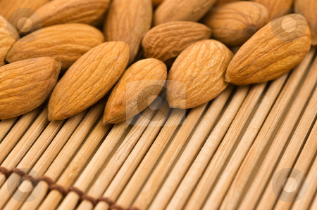Almonds on a bamboo mat stock photo, Group of almonds on a bamboo mat, close up. by Pablo Caridad