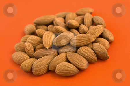 Almonds, orange background. stock photo, Group of almond kernels on orange background. by Pablo Caridad