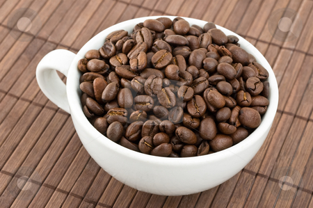 Coffe grains and cup stock photo, Coffe grains and cup on bamboo mat. by Pablo Caridad