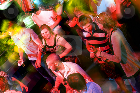 Busy dance floor stock photo, Girl smiling at the camera on a crowdy dance floor in a discotheque by Corepics VOF