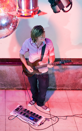 Guitarist on stage stock photo, Guitarist alone on stage in a club seen from above by Corepics VOF