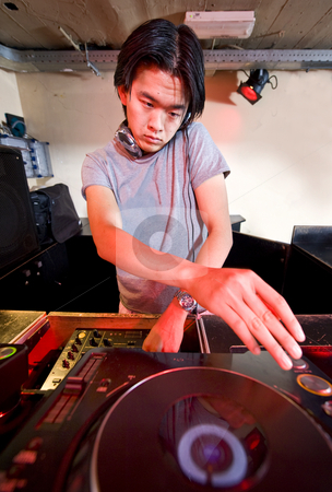 Mixing Dee Jay stock photo, Dee Jay behind the turntabls in a nightclub by Corepics VOF