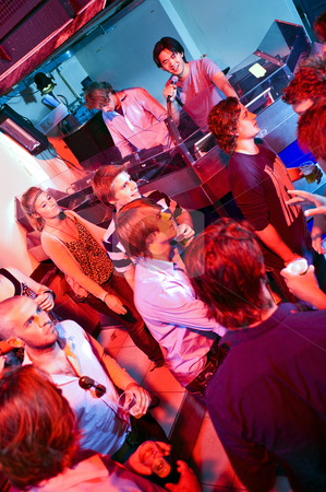Clubbing stock photo, Disc Jockey and Microphone Controller in a crowded club by Corepics VOF