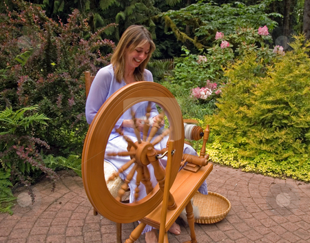 Woman Enjoying Craftsmanship stock photo, This woman is enjoying creating her craft of spinning raw wool into yarn with a spinning wheel in a peaceful garden. by Valerie Garner