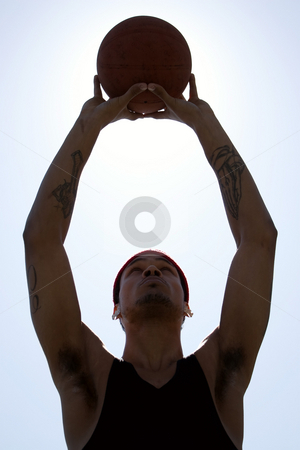 Basketball Player stock photo, A silhouette of a young basketball player holding the ball up to the sky. by Todd Arena