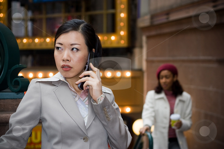 Business Woman On Her Phone stock photo, An attractive Asian business woman talking on her cell phone in the city. by Todd Arena
