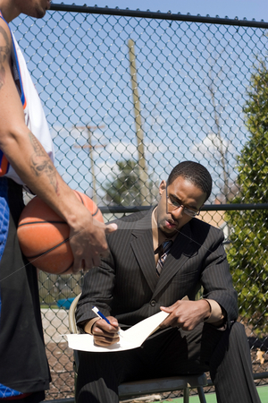 Basketball Coach stock photo, A basketball coach in a business suit sharing a play with a player on the team.  He could be also be a college scout trying to get him to sign a contract. by Todd Arena