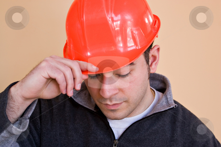Construction Worker stock photo, A young construction professional tips putting on his hard hat. by Todd Arena