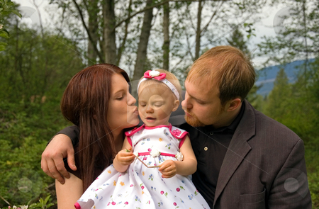 Cute Young Family Outside stock photo, This cute young Caucasian family is outdoors together and mom is kissing baby girl while dad embraces both. by Valerie Garner