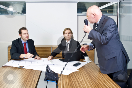 Business meeting stock photo, A business meeting with two young associates and a senior manager discussing plans and talking to a client on the phone by Corepics VOF