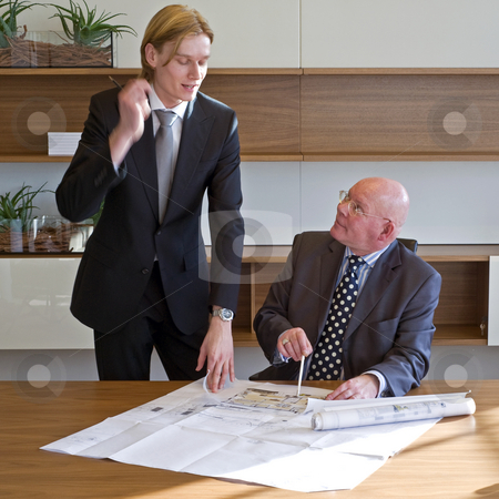 Validating designs stock photo, Young architect asking his boss to validate his designs, and discussing it animately, gesturing with his hand by Corepics VOF