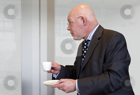 Profile of a manager stock photo, A bald headed manager drinking a cup of coffee in profile by Corepics VOF