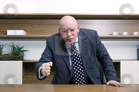 Angry Boss stock photo, An angry senior manager slamming his fist on the desk in front of him. by Corepics VOF