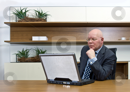 Thinking manager stock photo, A manager thinking hard behind a laptop by Corepics VOF