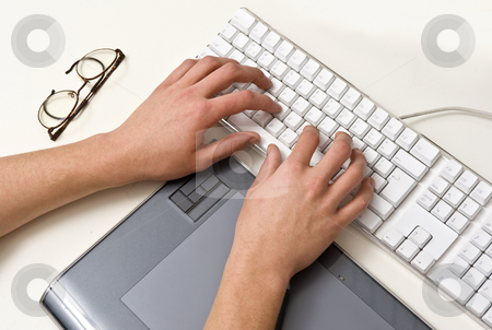 Typing Hands stock photo, Two typing hands on a white keyboard, with a pair of glasses and a tablet, situated in an office environment by Corepics VOF