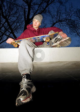 Skateboarder stock photo, An unhappy looking youth with a skateboard in his hand sitting on the concrete ledge of a bunker by Corepics VOF