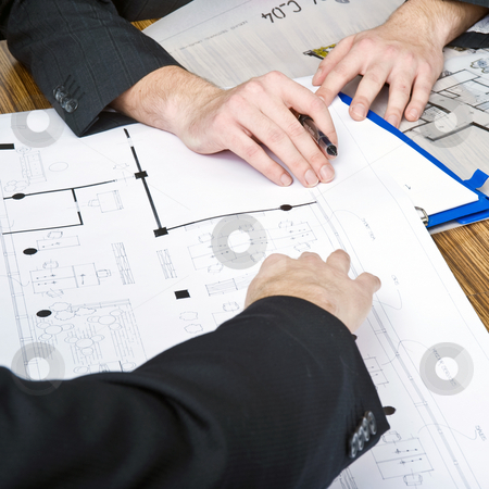 Discussing architectural plans stock photo, A close up of several hands going over architectural plans and drawings during a business meeting by Corepics VOF