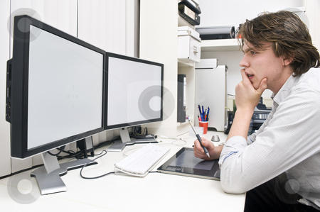 At work stock photo, A young man at work behind a dual monitor work station in a design studio office environment by Corepics VOF