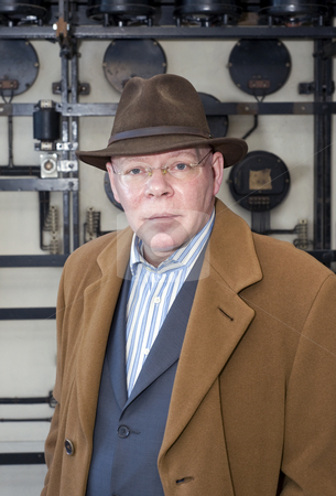 Senior Citizen stock photo, A kind looking senior man with a faint smile wearing a brown overcoat against a grungy, industrial background by Corepics VOF