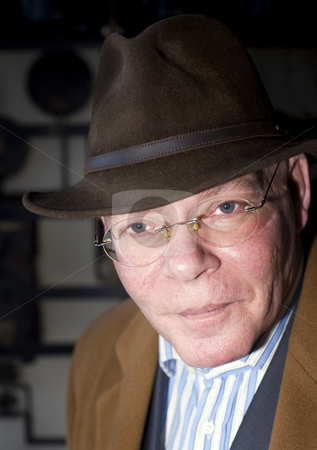 Senior Man stock photo, A rich contrast close up portrait of a senior man, slightly leaning forward, wearing a hat and overcoat against a grungy looking industrial background by Corepics VOF