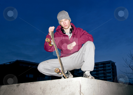 Skateboarder stock photo, Lifestyle portrait of an unhappy looking youth with a skateboard in his hand sitting on the concrete ledge of a bunker by Corepics VOF