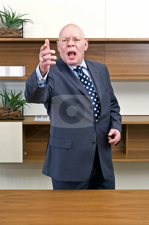 Angry Boss stock photo, An angry, gesturing, bold headed senior manager standing behind his desk, yelling and shouting by Corepics VOF