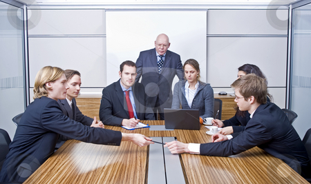 Board Meeting stock photo, Seven people in a cubicle, preparing for a management team meeting by Corepics VOF