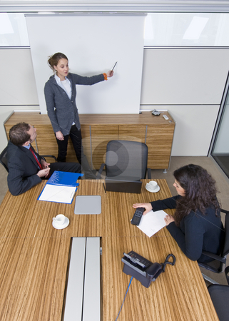Meeting room presentation stock photo, Three young business associates in a meeting, one presenting a theory in front of a white screen. by Corepics VOF