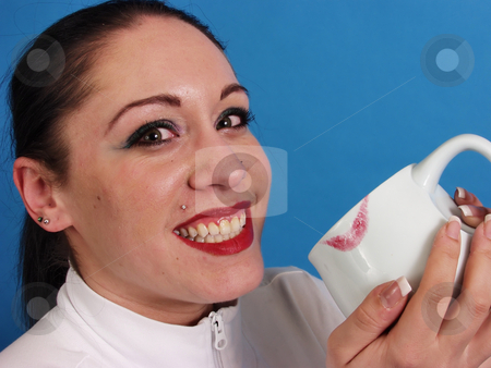 Lipstick Kiss on Cup stock photo, A beautiful brunette smiles broadly for the camera, a coffee cup with a deep red lip print on the rim is cradled in her hands. On a blue background. by Robert Gebbie