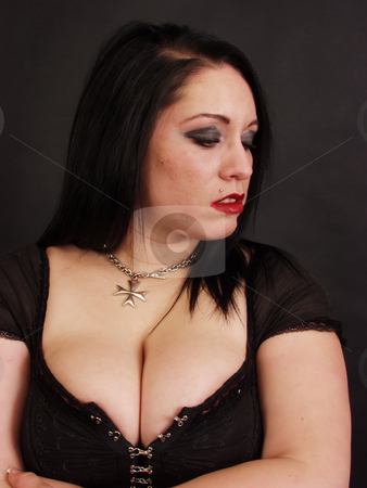 It Doesn't Matter Anymore stock photo, Portrait of a sad young goth woman with dramatic eyes and ruby red lips on a black background. by Robert Gebbie