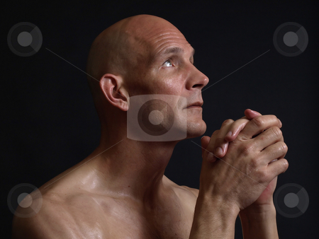 Praying Man stock photo, A bald shirtless man clasps his hands in prayer, eyes pleading skyward, over a black background. by Robert Gebbie