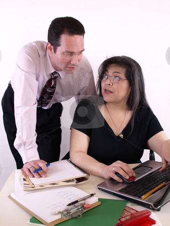Helping a Coworker stock photo, A male and female working together in the office at the computer. Isolated against a white background. by Robert Gebbie