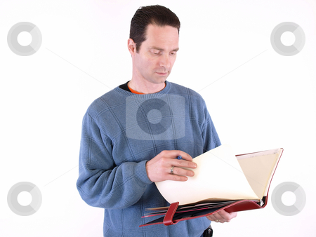 Checking the Report stock photo, An adult male looking over notes in a binder, isolated against a white background. by Robert Gebbie