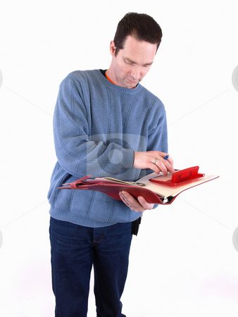 Checking the Figures stock photo, An adult male in blue checks over some figures in a binder. Isolated on a white background. by Robert Gebbie