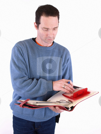 Taking Measurements stock photo, An adult male in blue checks over some measurements in a binder. Isolated on a white background. by Robert Gebbie
