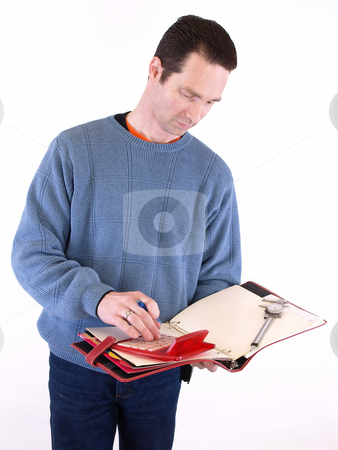 Working on Measurements stock photo, An adult male in blue checks over some measurements in a binder. Isolated on a white background. by Robert Gebbie