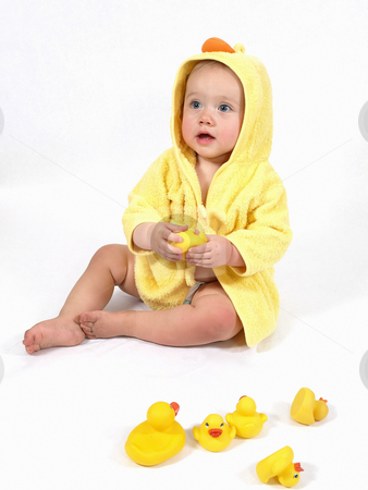 Girl with Her Ducks stock photo, A baby girl in a yellow duck bathrobe holds a plastic toy rubber duck. by Robert Gebbie