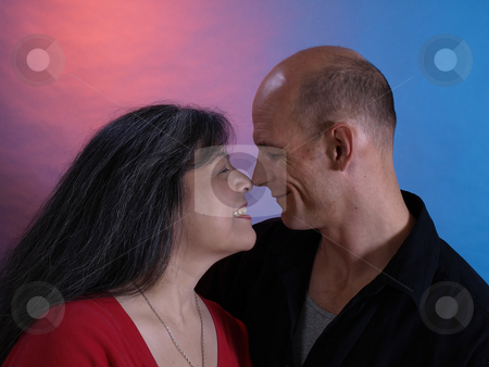 Nose to Nose stock photo, A happy middle aged couple touch their noses together. by Robert Gebbie