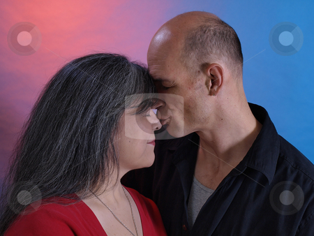Nose Kisses stock photo, An older couple show signs of affection toward eachother. by Robert Gebbie