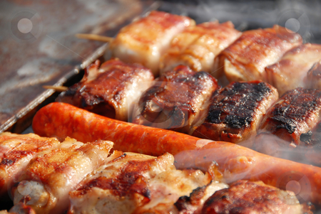 Meat on barbecue stock photo, Various meat grilled on barbecue in smoke closeup by Julija Sapic