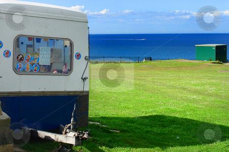 Ice cream van stock photo, Greem grass field, cloudy blue sky ocean and Ice cream van. by Marc Torrell