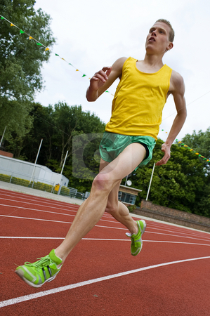 Running athlete in mid-air stock photo, Running athlete on a middle distance race on an oval track in mid-air by Corepics VOF