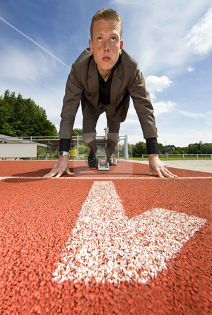 Number one in business stock photo, Being number one in business - businessman in the starting blocks on a running track in the first lane by Corepics VOF