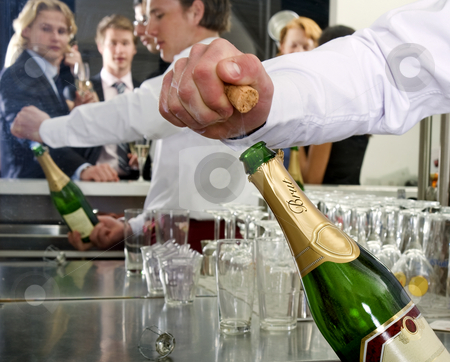 Opening a bottle of Champagne stock photo, A bar man opening a bottle of champagne behind a bar, with several people reflected in the mirror behind him by Corepics VOF