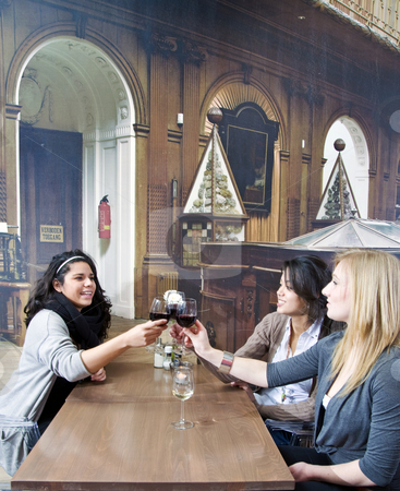Girl talk stock photo, Three women at a restaurant table, toasting their glasses of wine by Corepics VOF