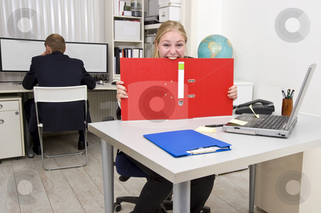Businesswoman going insane stock photo, Businesswoman biting a dossier out of frustration, with an oblivious colleague in the background by Corepics VOF